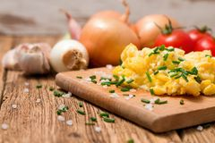 Scrambled eggs with chopped chive on wooden board Royalty Free Stock Image