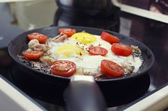 Scrambled eggs cooking in a frying pan, cooking on a ceramic stove, fried eggs with bacon and tomato, front view closeup royalty free stock photo
