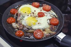 Scrambled eggs cooking in a frying pan, cooking on a ceramic stove, fried eggs with bacon and tomato, 45 view closeup stock photography