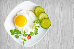 Scrambled eggs with cucumbers and tomatoes on plate on wooden table, Stock Images