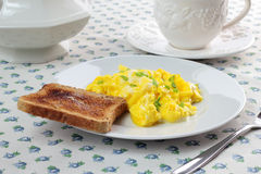 Scrambled eggs, cup of coffee and toast. Scrambled eggs and piece of toast on white plate. Cup of coffee Stock Photo