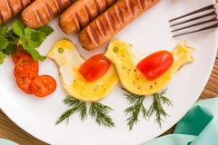 Scrambled eggs in the form of birds, sausages and tomatoes. On a plate. Top view Royalty Free Stock Photo