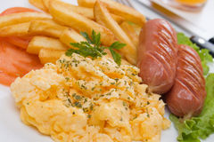 Scrambled eggs with french fries and sausage Royalty Free Stock Photos