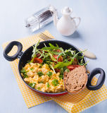 Scrambled eggs with fresh salad in frying pan Stock Photo