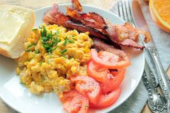 Scrambled eggs with fresh tomatoes and fried bacon Stock Image