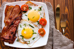 Scrambled eggs, fried bacon and cherry tomatoes on a white plate Royalty Free Stock Photography