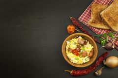 Scrambled eggs with fried bacon. English breakfast. Toast and scrambled eggs with chives. Royalty Free Stock Photography