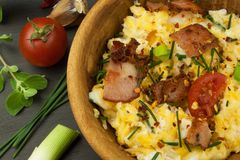 Scrambled eggs with fried bacon. English breakfast. Toast and scrambled eggs with chives. Stock Image