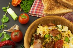 Scrambled eggs with fried bacon. English breakfast. Toast and scrambled eggs with chives. Royalty Free Stock Photo