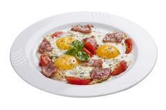 Scrambled eggs with ham and tomatoes on a white plate. Lobio from green beans on a white plate on white background royalty free stock photo