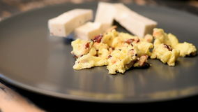Scrambled eggs with hazelnuts and cheese stock video