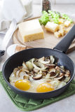 Scrambled eggs with mushrooms to frying pan, sliced cheese and herbs Royalty Free Stock Photos