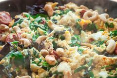 Scrambled eggs omelet frittata with spinach, sausages and cashew nut. In a frying pan on a wooden table in front of the window. Selective soft focus stock image