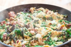Scrambled eggs omelet frittata with spinach, sausages and cashew nut. In a frying pan on a wooden table in front of the window. Selective soft focus stock photos
