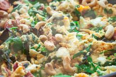 Scrambled eggs omelet frittata with spinach, sausages and cashew nut. In a frying pan on a wooden table in front of the window. Selective soft focus royalty free stock photography