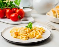 Scrambled eggs, Omelette. Breakfast with pan-fried eggs, cup of royalty free stock images