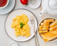 Scrambled eggs, Omelette. Breakfast with pan-fried eggs, cup of. Tea, tomatoes on white stone marble background. Top view royalty free stock image