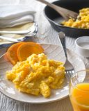 Scrambled Eggs with Orange Slices. A plate of delicious fresh scrambled eggs with orange slices and orange juice royalty free stock photos