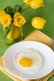 Scrambled eggs and oranges for breakfast and yellow jug with tulips Stock Photography