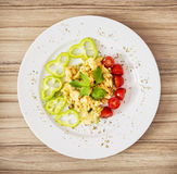Scrambled eggs with paprika, cherry tomatoes and celery leaves, Stock Photo