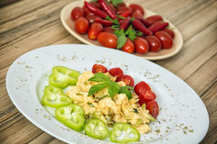 Scrambled eggs with paprika, cherry tomatoes, chili peppers and Royalty Free Stock Photography