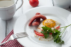 Scrambled eggs on a plate with pieces of tomato and sausage Stock Photography