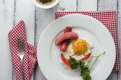 Scrambled eggs on a plate with pieces of tomato and sausage Royalty Free Stock Photos