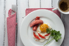 Scrambled eggs on a plate with pieces of tomato and sausage Royalty Free Stock Image