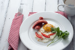 Scrambled eggs on a plate with pieces of tomato and sausage Royalty Free Stock Photo