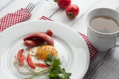 Scrambled eggs on a plate with pieces of tomato and sausage Stock Image