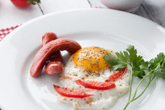 Scrambled eggs on a plate with pieces of tomato and sausage Royalty Free Stock Photography