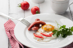 Scrambled eggs on a plate with pieces of tomato and sausage Royalty Free Stock Images