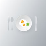 Scrambled eggs on plate. With spoon, fork and knife Royalty Free Stock Photos