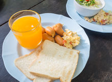 Scrambled eggs with pork sausages, bread and orange juice. On wood table, american breakfast Royalty Free Stock Photo