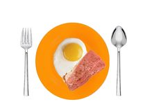 Scrambled eggs and roasted bacon with spices on orange plate Royalty Free Stock Photography