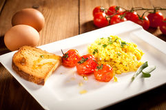 Scrambled eggs with roasted cherry tomatoes Stock Photos