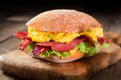 Scrambled eggs sandwich. Ciabatta sandwich with scrambled eggs, crispy bacon and lettuce leaves Royalty Free Stock Image