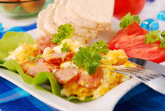 Scrambled eggs with sausage. And parsley for breakfast Royalty Free Stock Images
