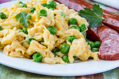 Scrambled eggs and sausage. Scrambled eggs with fresh green peas and sausage Royalty Free Stock Images