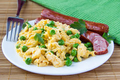 Scrambled eggs and sausage. Scrambled eggs with fresh green peas and sausage Stock Image