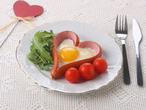 Scrambled eggs and sausage. Serving Valentine's Day Stock Photo