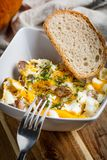 Scrambled eggs with sausage and bread. Tasty breakfast - scrambled eggs with sausage and bread Stock Photography