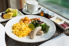 Scrambled eggs and sausage served with salad and hash browns Royalty Free Stock Photography