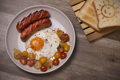 Scrambled eggs with sausages, tomatoes cherry and onion Stock Photo