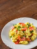 Scrambled eggs with shrimp and green onions in white plate on wooden table royalty free stock photo