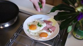 Scrambled eggs sunny side up on a plate with sausage. The girl l. Ays on a plate of pan stock video