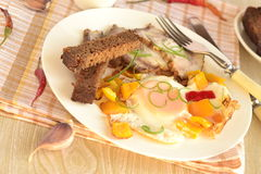 Scrambled eggs with sweet peppers, baked pork and rye toast Stock Image