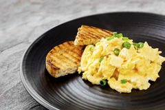 Scrambled Eggs with Toast on Black Plate Stock Images