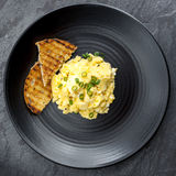 Scrambled Eggs with Toast on Black Plate Stock Photos