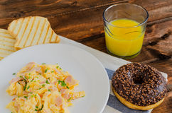 Scrambled eggs with toast and donut Stock Photography